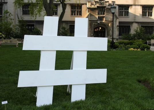 Simbolo in legno di hashtag in un prato